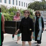 Member Carol Paris joins mock funeral procession in Washington, DC